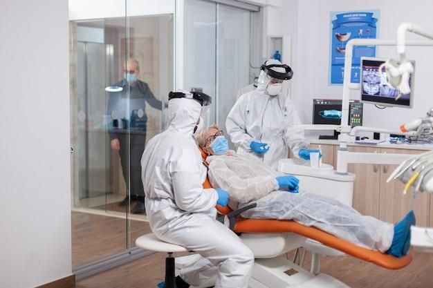 歯科医院でコロナウイルス中に化学防護服を着ている年配の患者歯科医院での診察中に防護服を着た年配の女性