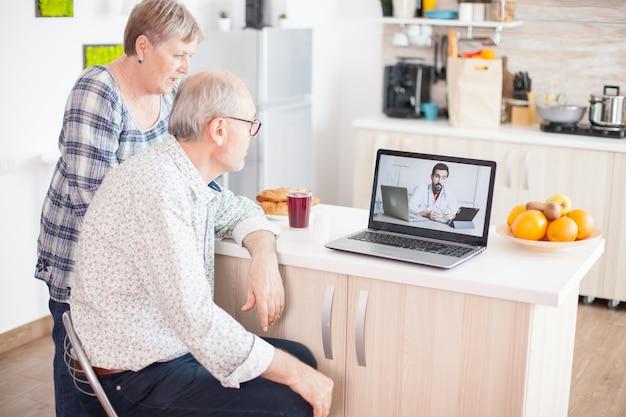 キッチンでラップトップを使用して医師とのビデオ会議のシニア患者。高齢者のためのオンライン健康相談薬の症状に関する病気のアドバイス、医師の遠隔医療ウェブカメラ。医療インテ