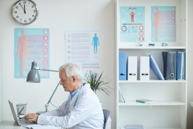 Старший педиатр работает на ноутбуке