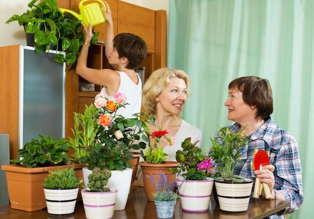 Старшие пенсионеры и девочка, ухаживающие за домашними растениями