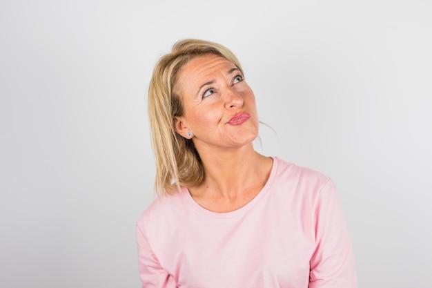 Senior pensive woman in rose blouse
