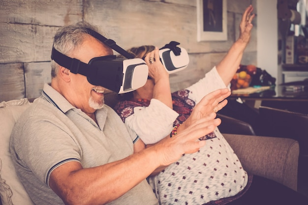 Senior people couple enjoying at home the new goggled headset technology with glasses and virtual reality