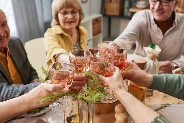 Senior people drinking red wine while sitting at dining table and celebrating some event together
