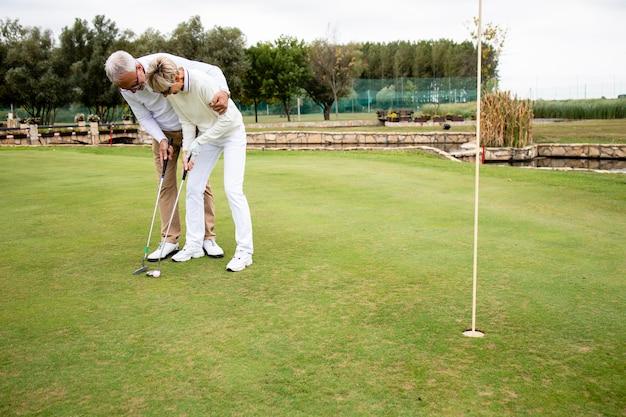 Пожилые люди наслаждаются свободным временем на пенсии и учатся играть в гольф на поле