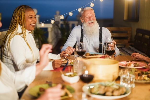 パティオディナーパーティーで楽しんでいる高齢者-流行に敏感な男性の顔に焦点を当てる