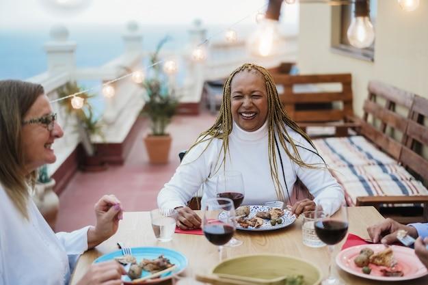 Пожилые люди весело едят и пьют вино за ужином во внутреннем дворике - сосредоточьтесь на лице афро-американской женщины