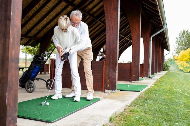 골프 코스에서 골프를 치는 방법을 배우는 은퇴한 노인들.