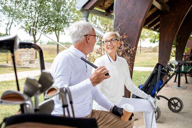 Старшие пенсионеры разговаривают и смеются перед тренировкой в гольф.