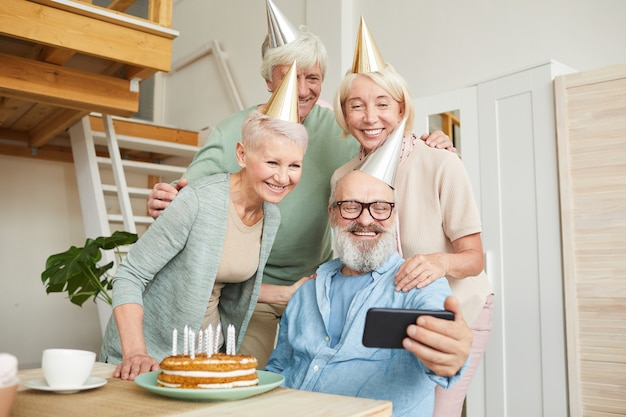 パーティーでバースデーケーキと一緒にテーブルに座って携帯電話で自分撮りの肖像画を作る高齢者