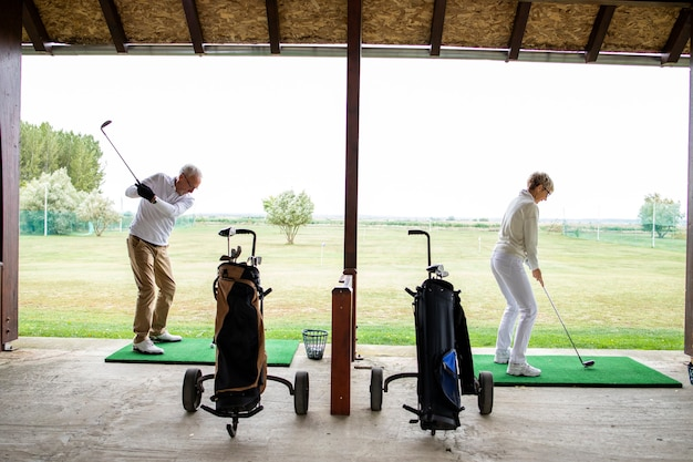 Пожилые люди или игроки в гольф на поле для гольфа, практикующие дальние удары.