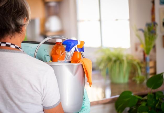 灰色のプラスチック製のバケツを持って家事の準備ができている高齢者
