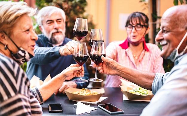 열린 얼굴 마스크를 착용하는 레스토랑 바에서 와인을 토스트하는 노인-안경에 초점