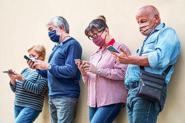 얼굴 마스크가있는 스마트 폰을 사용하는 노인들