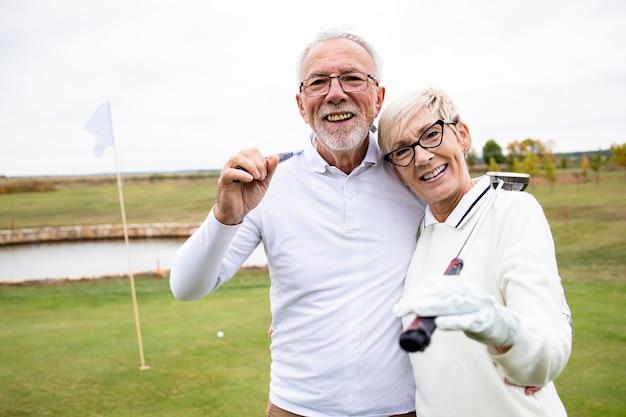 Пожилые люди с клюшками для гольфа, играющие в свою любимую спортивную игру и наслаждающиеся временем отдыха