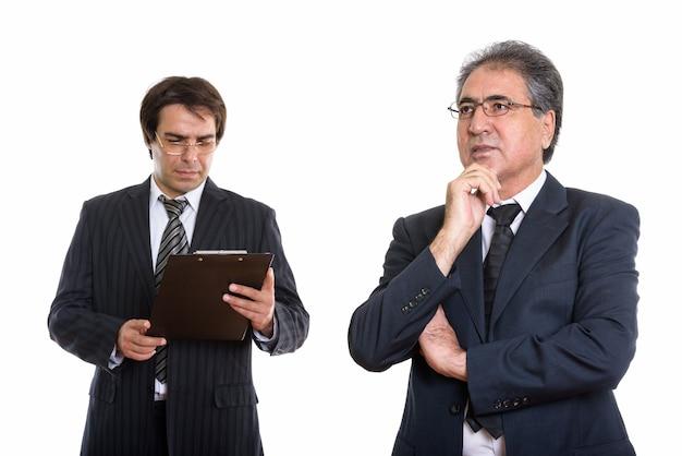 シニアペルシャのビジネスマンの思考とクリップボードを見て若い同僚