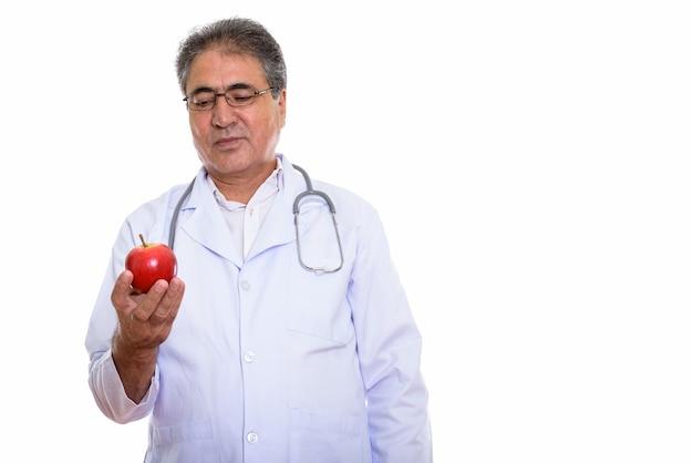 Старший персидский доктор мужчина держит и смотрит на красное яблоко