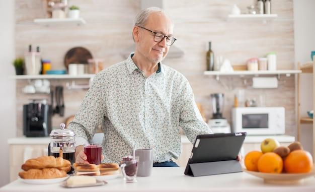 健康的なライフスタイルを持っている朝食時にキッチンでタブレットpcを閲覧している高齢者。モバイルアプリ、現代のインターネットオンライン情報を使用して定年のタブレットポータブルパッドpcを持つ高齢者
