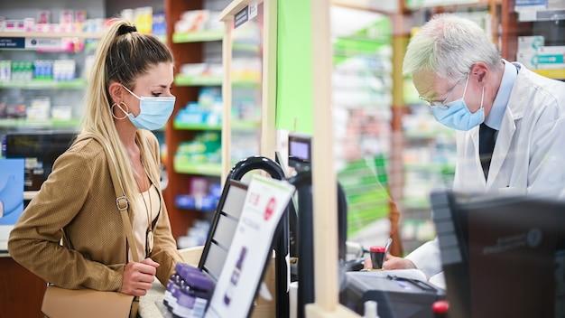 コロナウイルスのためマスクを着用している顧客を扱う上級薬剤師