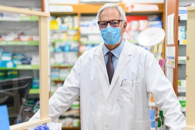 Senior pharmacist wearing a protective mask in his store, coronavirus concept