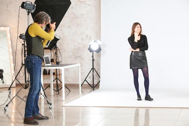 Старший фотограф, работающий с моделью в студии
