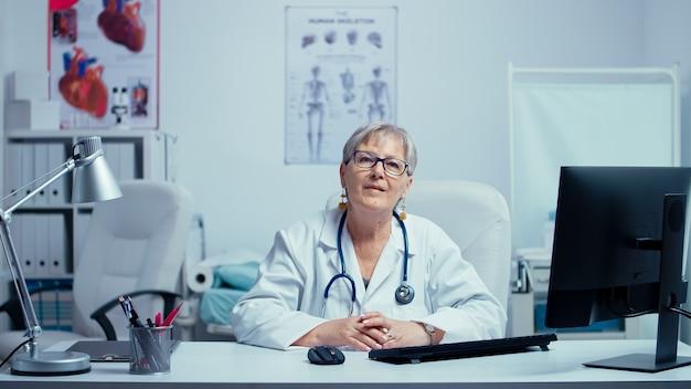 Старший врач, улыбаясь в камеру в современной частной клинике больницы с кроватью в фоновом режиме. современная частная больница, кабинет врача, кабинет врача, семейный терапевт, медленное движение.