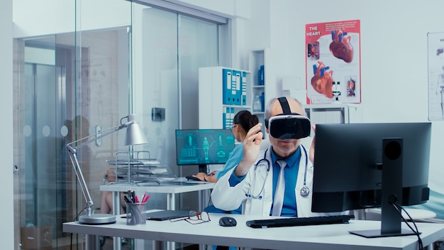 Старший врач использует очки виртуальной реальности в современной частной клинике для изучения заболеваний в виртуальном пространстве и современных технологиях. на заднем плане современная клиника со стеклянными стенами и пациенты с врачами в холле.