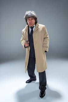 Старший полицейский агент с ружьем выступает в роли детектива или босса мафии. студия выстрелил на серый в стиле ретро