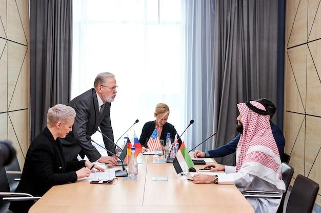 Старший политик предлагает свой план действий и разделяет мнение, пожилой мужчина в костюме разговаривает с многоэтнической группой партнеров, сидящих за столом в зале заседаний, обсуждая
