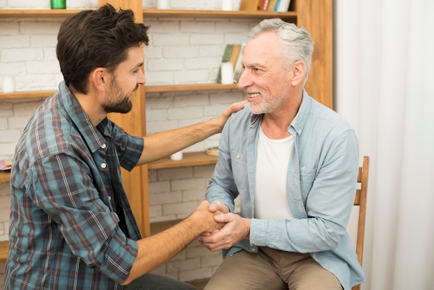 Senior positive man shaking hands with young happy guy in room