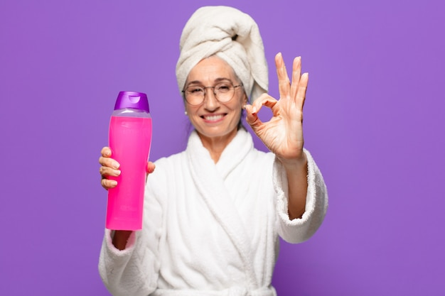 Senior pre woman after shower wearing bathrobe. facial cleaning or shower products concept