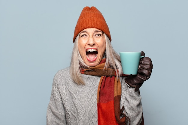 겨울 옷을 입고 커피 컵 수석 전 여자. 겨울 개념