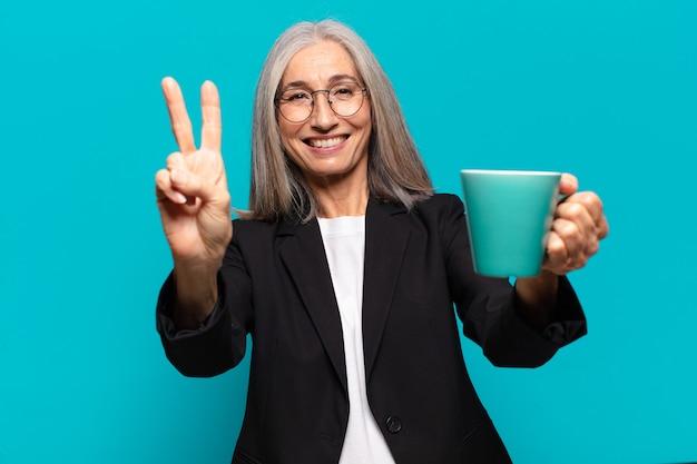 Старший довольно бизнесвумен с чашкой кофе