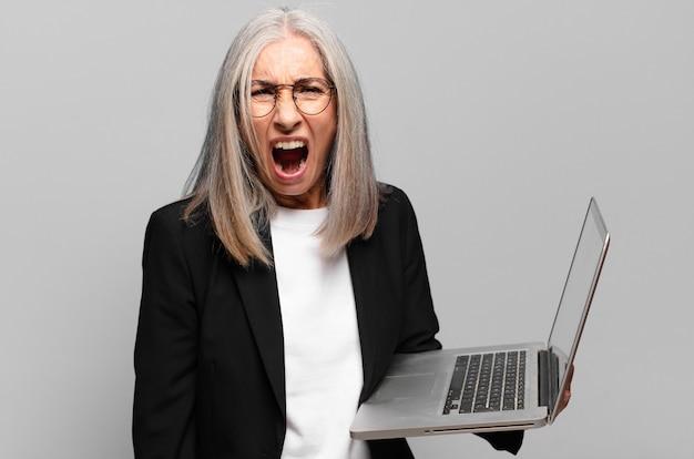 Старший довольно бизнесвумен с ноутбуком