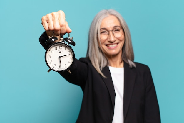 Senior pretty businesswoman with an alarm clock. time concept