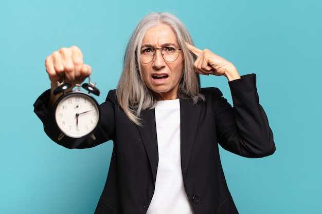 Senior pretty businesswoman with an alarm clock.