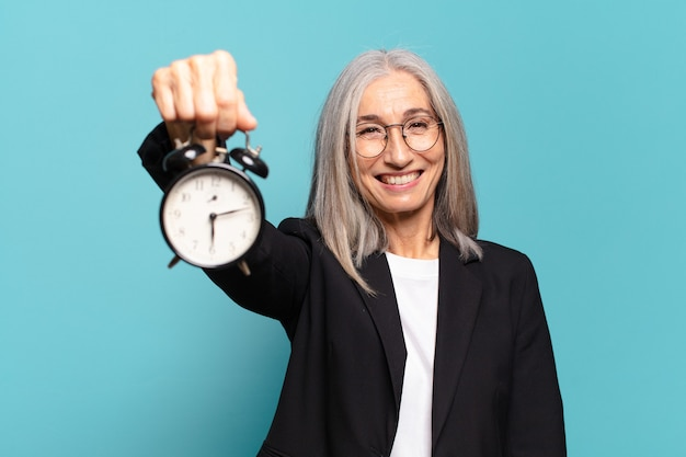Senior pretty businesswoman with an alarm clock