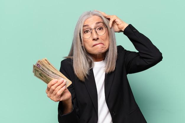 Senior pretty businesswoman with dollar banknotes. money concept