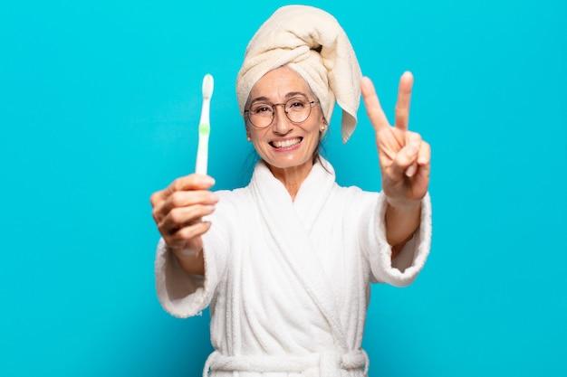 목욕 가운을 입고 칫솔로 샤워 후 수석 예쁜 여자
