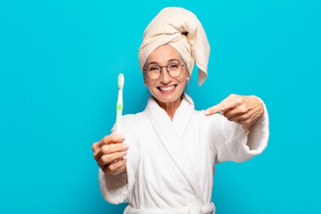 Старшая красивая женщина после душа в халате и с зубной щеткой