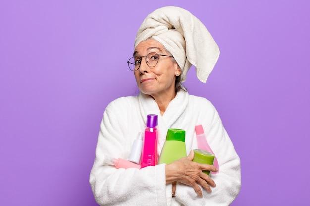 목욕 가운 입고 샤워 후 수석 예쁜 여자입니다. 얼굴 청소 또는 샤워 제품 개념