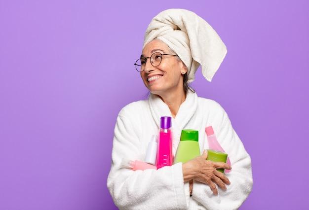 バスローブを着てシャワーを浴びた後の年配のきれいな女性。フェイシャルクリーニングまたはシャワー製品のコンセプト