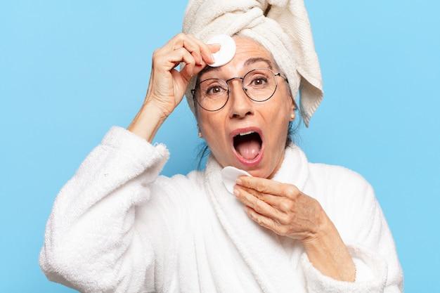 シニアきれいな女性の顔のクリーニングまたはバスローブを着てシャワーの後のメイクアップ