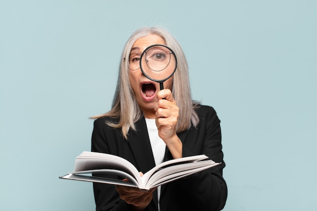 本と虫眼鏡を持つ年配のきれいな女性。検索コンセプト