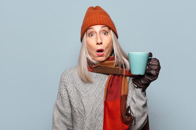 겨울 옷을 입고 커피 컵 수석 예쁜 여자. 겨울 개념