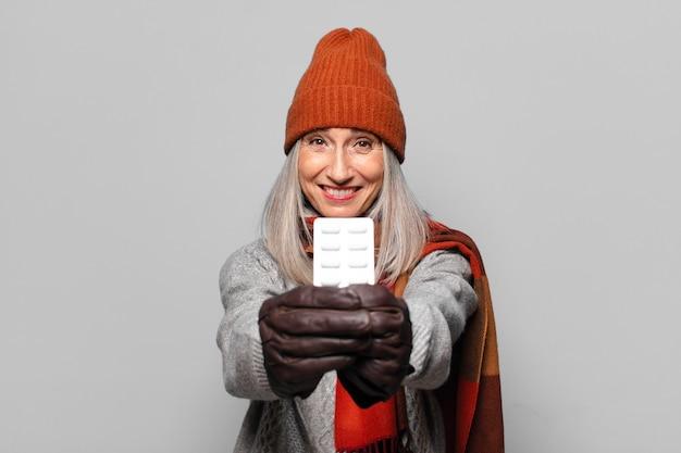 冬の服を着て錠剤タブレットを持つ年配のきれいな女性。インフルエンザの概念