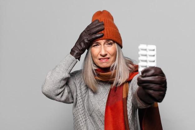 冬の服を着た錠剤タブレットを持つシニアのきれいな女性。インフルエンザの概念
