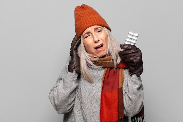 冬の服を着て錠剤タブレットを持つ年配のきれいな女性
