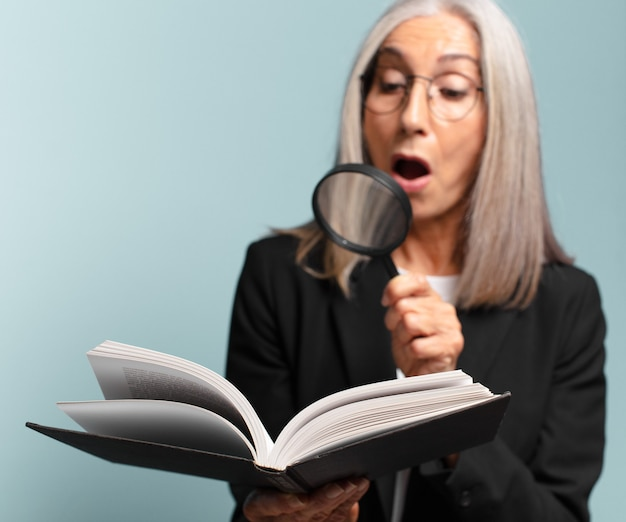 Senior pretty woman with a book and a magnifying glass. search concept