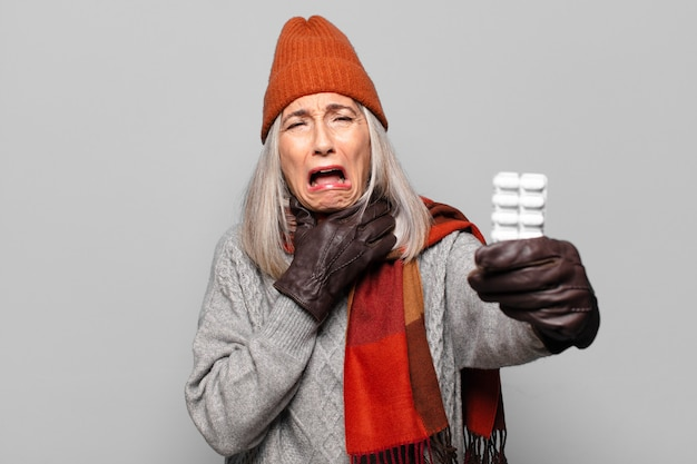 Senior pretty woman with a pills tablet wearing winter clothes. flu concept
