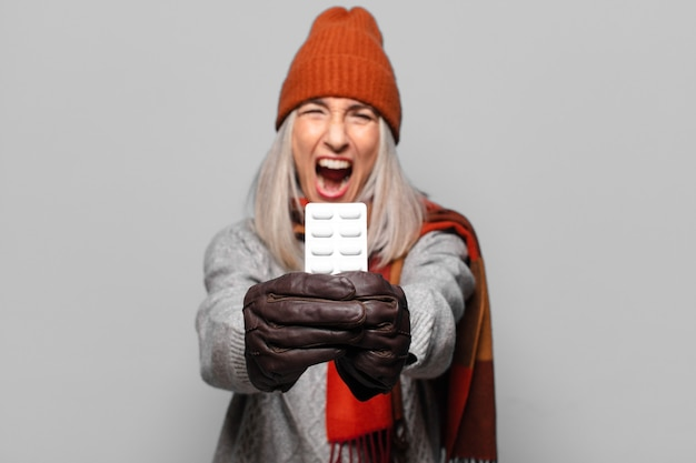 Senior pretty woman with a pills tablet wearing winter clothes.